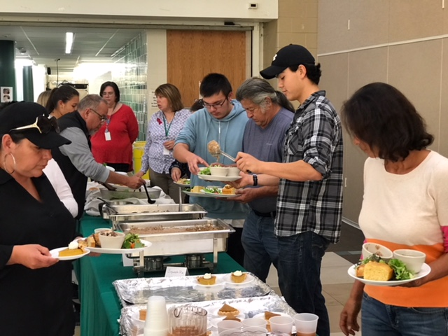 A group of adults surround a buffet table with trays of food, as they serve themselves a meal