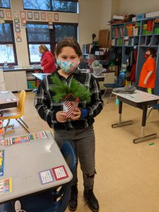 student with centerpiece of tree greens